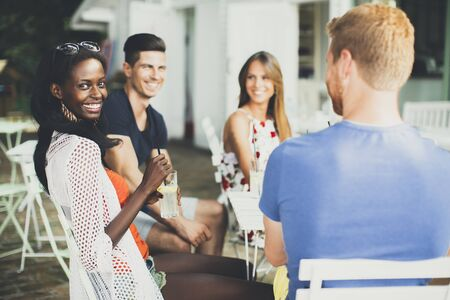 men talking: Young multiracial friends in the cafe at summer