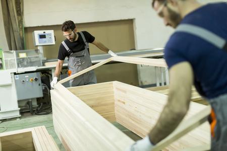 Jonge mannelijke arbeiders in een fabriek voor de productie van meubels