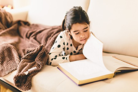 girl lying down: Little girl lying down on sofa and reading book Stock Photo