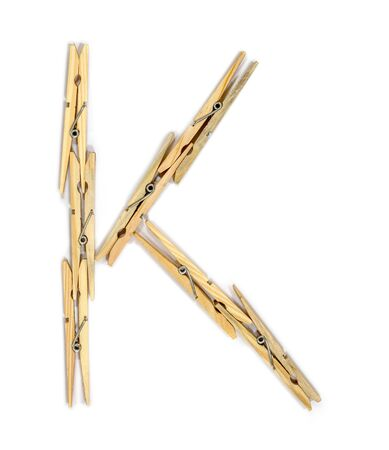 Letter K made of wooden clothespins isolated on white