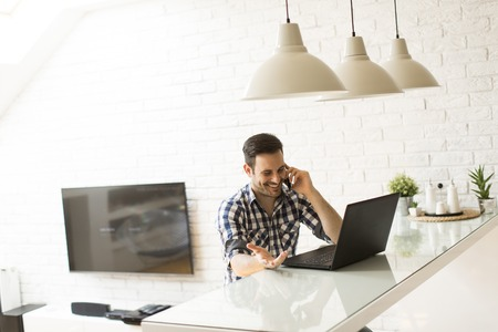 notebook computer: View at man with a laptop and a phone at home Stock Photo