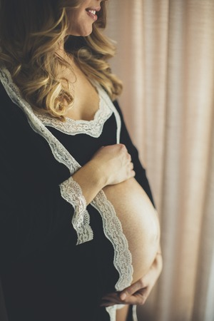 Photo of beautiful pregnant woman wearing lingerie and posing in the room by window