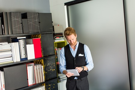 handome: Handome young man with tablet in the office Stock Photo