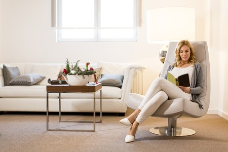 Young woman reading a book and sitting on comfortable chair at home 스톡 콘텐츠