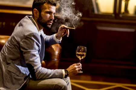 Young man tasting white wine and smoking cigar Stock Photo