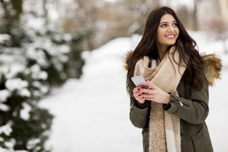 Young woman using a phone in the winter park