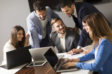 couching: Young successful managers discussing new business project in modern office