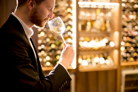 Young man tasting white wine in bar Stock Photo