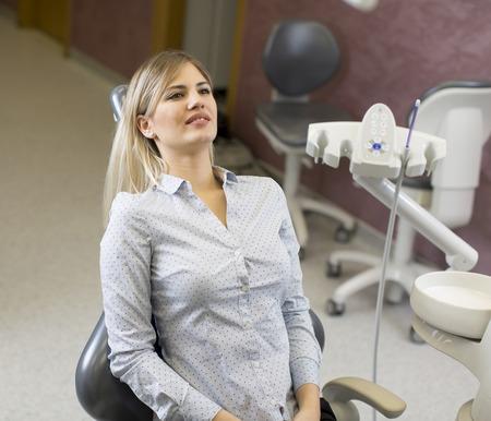 Frau sitzt auf dem Stuhl in der Zahnarztpraxis