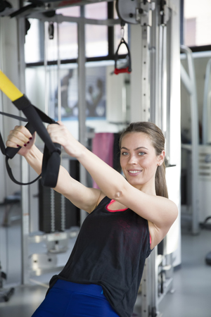 Women doing push ups training arms with trx fitness straps in the gym Stock Photo