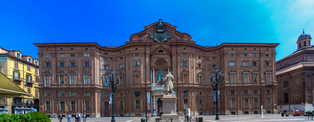 TURIN, ITALY - JUNE 3, 2015: Unidentified people in front of the Palazzo Carignano is a historical building in the centre of Turin, Italy, which houses the Museum of the Risorgimento. Its rounded façade is different from other façades of the same struc