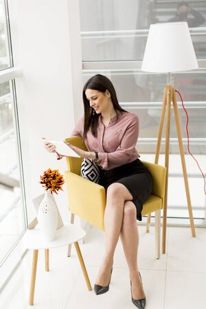 Young businesswoman sitting on a chair and holding  tablet in  hands