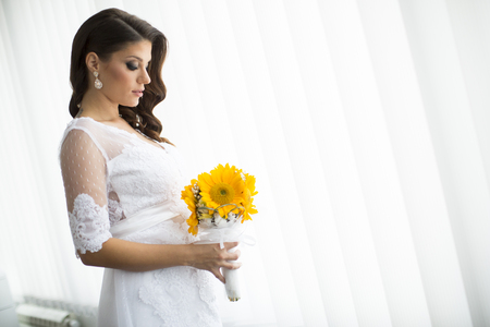 Pregnant bride with a bouquet of sunflowers photo