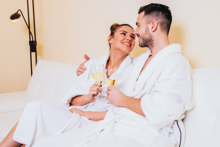 Loving couple drinking white wine in a bathrobe in a spa center