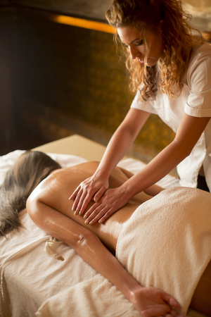 Beautiful brunette spa woman getting massage on towel in spa salon photo