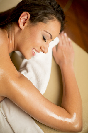 Close up portrait of a beautiful young woman lying on massage table at spa center photo