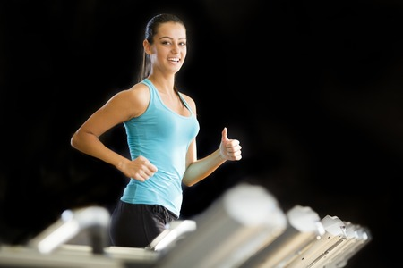 Young woman exercise on the treadmill at the gym photo