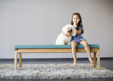 Little girl playing with white poodle in the room Stock Photo