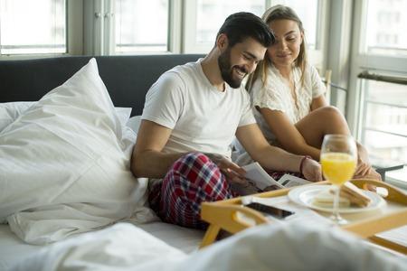 Pareja tomando el desayuno en su cama en su casa Foto de archivo - 75731036