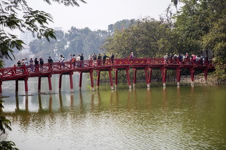 HANOI, VIETNAM - MARCH 2, 2017: Unidentified people at Huc bridge in Hanoi, Vietnam. This wooden red bridge connect Jade Island with shore  at Hoan Kiem lake.