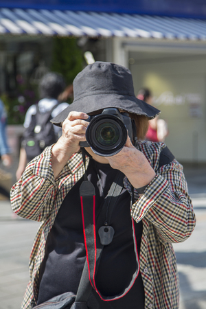 TOKYO, JAPAN - OCTOBER 2, 2016: Unidentified man taking photo on the street in Ginza, Tokyo. Ginza is a popular upscale shopping area of Tokyo.