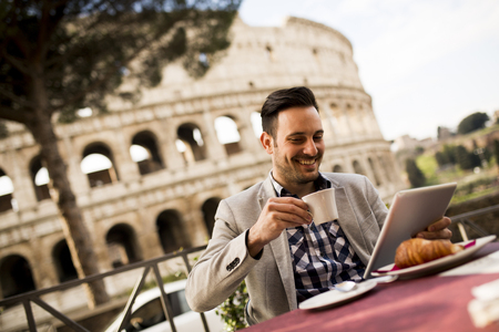 oung man sitting and having a cup of coffee in Rome, Italy