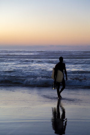 CASABLANCA, MOROCCO - SEPTEMBER 10, 2014: Unidentified surfer on the beach at Casablanca, Morocco. Casablanca offers several surf spots in the city area. Imagens - 79201306