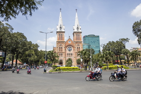 HO CHI MINH, VIETNAM - FEBRUARY 22, 2017: Unidentified people by Notre Dame Cathedral Basilica of Saigon in Ho Chi Minh, Vietnam. It is  	Roman Catholic church consecrated at 1880. Stock Photo - 76511209