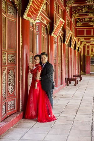 HUE, VIETNAM - FEBRUARY 19, 2017: Unidentified wedding couple at Royal Palace in Hue, Vietnam. Traditional Vietnamese wedding is one of the most important ceremonies in Vietnamese culture Sajtókép