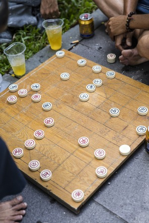 HO CHI MINH, VIETNAM - FEBRUARY 22, 2017: Unidentified man playing traditional Chinese chess on Ho Chi Minh sidewalk in Vietnam. It is one of the most popular board games in China.