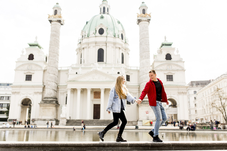 Young couple walking holding hands around Vienna