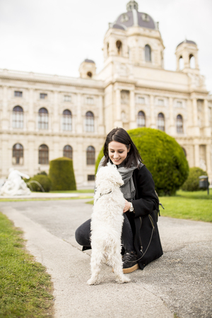 Beautiful happy young woman with cute small dog puppy have fun on street Reklamní fotografie