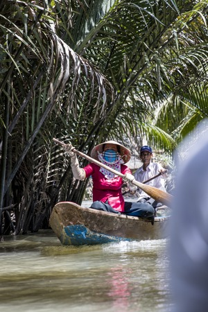 MEKONG DELTA, VIETNAM - FEBRUARY 21, 2017: Unidentified people in the boat at Mekong Delta in Vietnam. Boats are the main means of transportation in Mekong Delta.