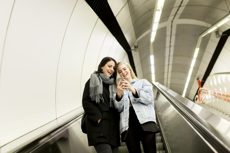 Young women use escalators and using a mobile phone