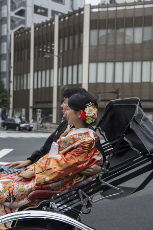 TOKYO, JAPAN - OCTOBER 3, 2016: Unidentified people riding on rickshaw at Asakusa district in Tokyo, Japan. Rickshaws are believed to have been invented in Japan in the 1860s