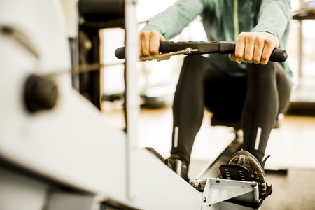 Young man training on rowing machine in the gym Stock Photo