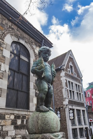 Bronze sculpture of a boy holding two fishes at Fischmarkt in Aachen, Germany Editorial