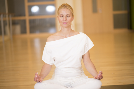 Beautiful young woman sitting in Lotos pose and practicing meditation in yoga studio Stock Photo
