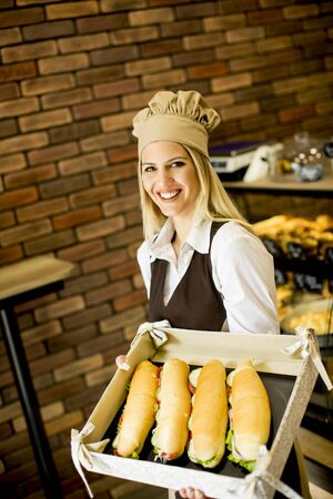 patisserie: Beautiful female bakery posing with various types of sandwiches in the baker shop