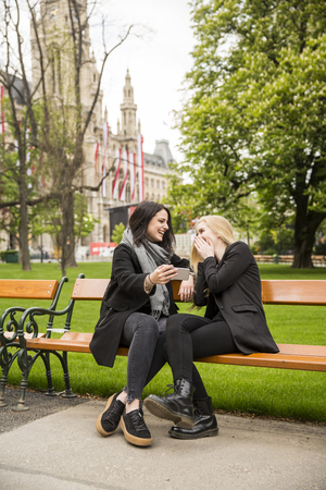 Two young women sitting on bench a park and watch something on a mobile phone Reklamní fotografie