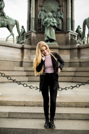 Young woman with mobile phone on the street of Vienna, Austria