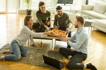 Young people eating pizza, drinking cider and have fun the room