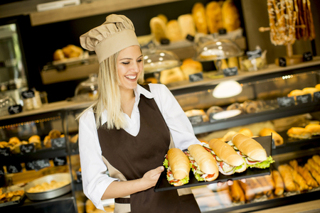 patisserie: Beautiful female bakery posing with various types of sandwiches in the bakery shop