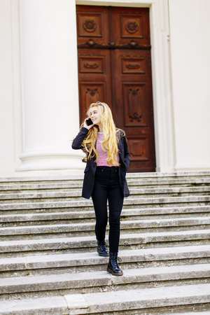 Young woman with mobile phone on the stairs in Vienna, Austria