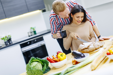 Happy young couple have fun in modern kitchen indoor while preparing vegetables food for lunch