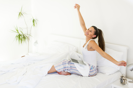 Young woman stretching in bed while her lap top standing on legs Banco de Imagens