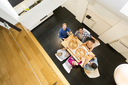 View at young people have a meal in the dining room in modern home, view from above