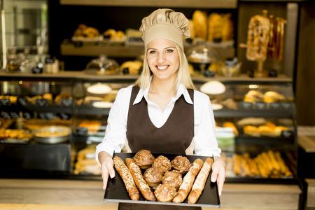 Mooie vrouwelijke bakkerij poseren met verschillende soorten gebak en brood in de bakker Stockfoto