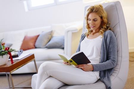 책을 읽고 집에서 편안한 의자에 앉아 젊은 여자가 볼