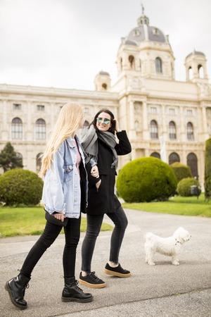 Beautiful happy women walking with a dog at the street of Vienna, Austria Reklamní fotografie